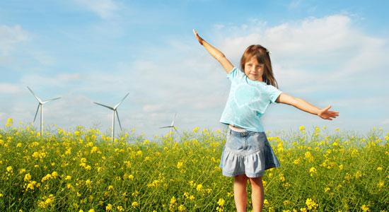Une fille dans un champs de fleurs de colza avec des eoliennes